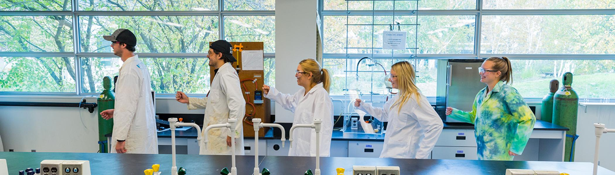 5 Chemistry students wearing white lab coats and safety glasses walking in single file in a chemistry lab with gas cylinders and equipment in the background