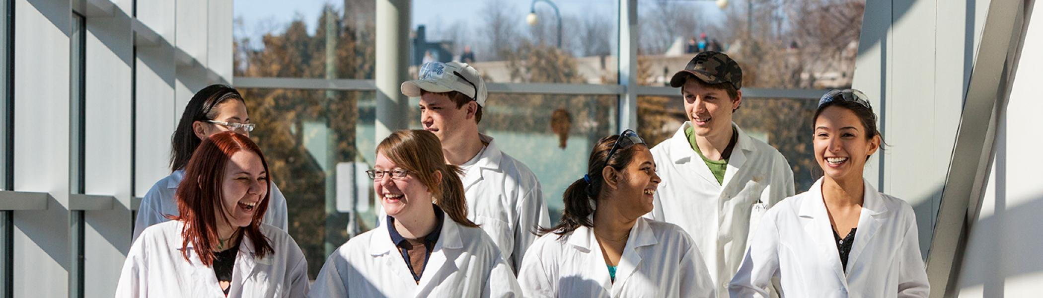 A group of 7 chemistry students walking in a hall smiling and talking, wearing white lab coats