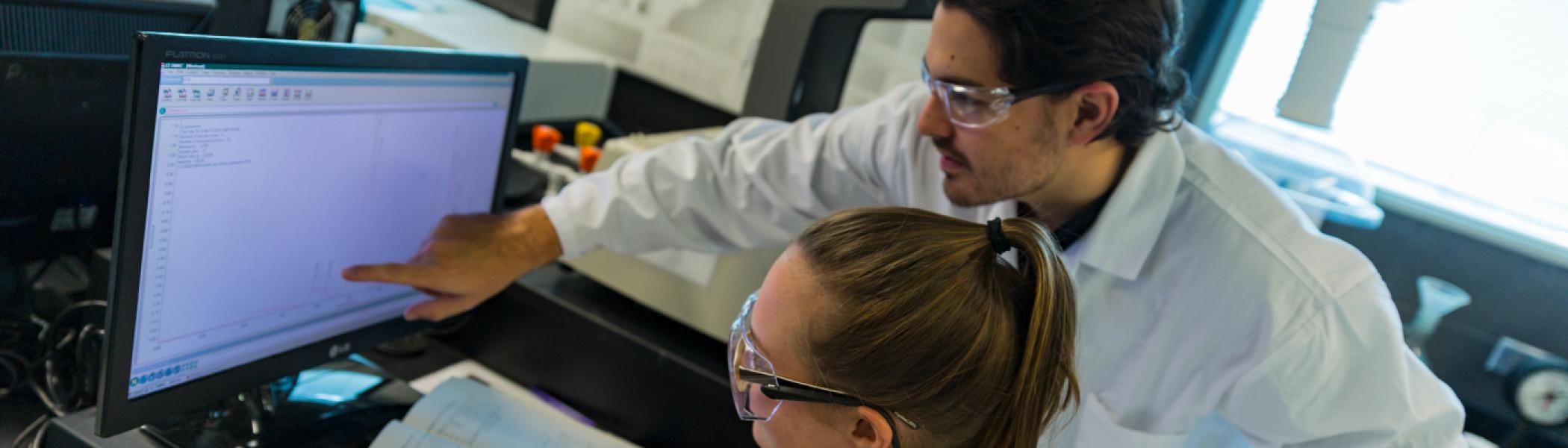 2 Chemistry students looking at an IR spectrum on a computer screen in a chemistry lab wearing white lab coats and safety glasses