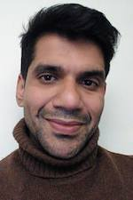 Omar Alam wearing a brown turtleneck sweater smiling at the camera
