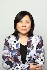 Wenying Feng wearing a purple and white blazer with her arms crossed facing the camera