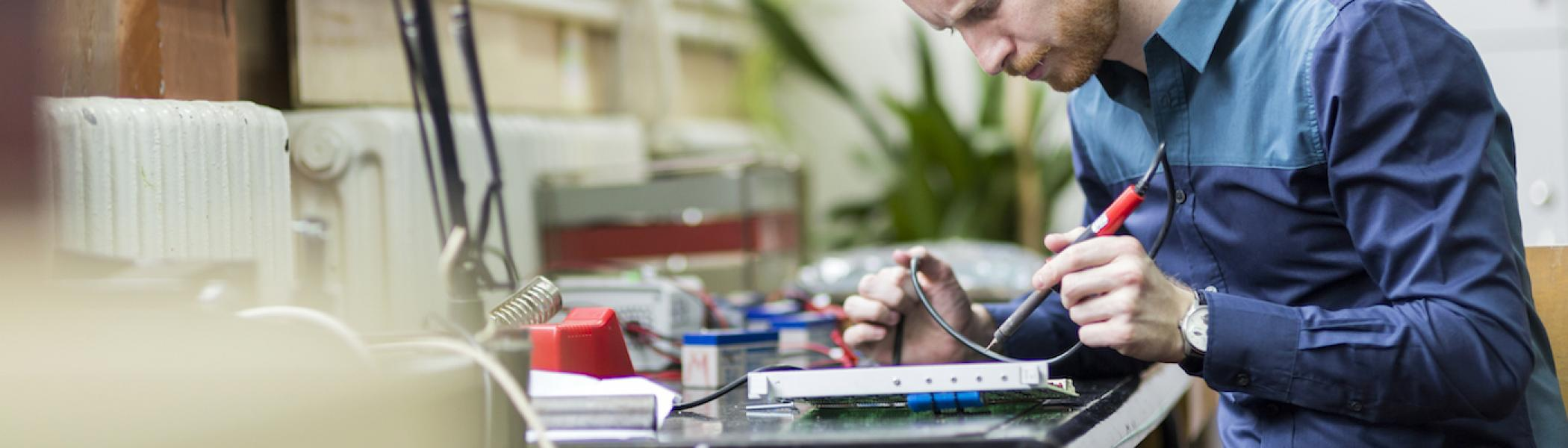 A guy working on a circuit board and concentrating on it