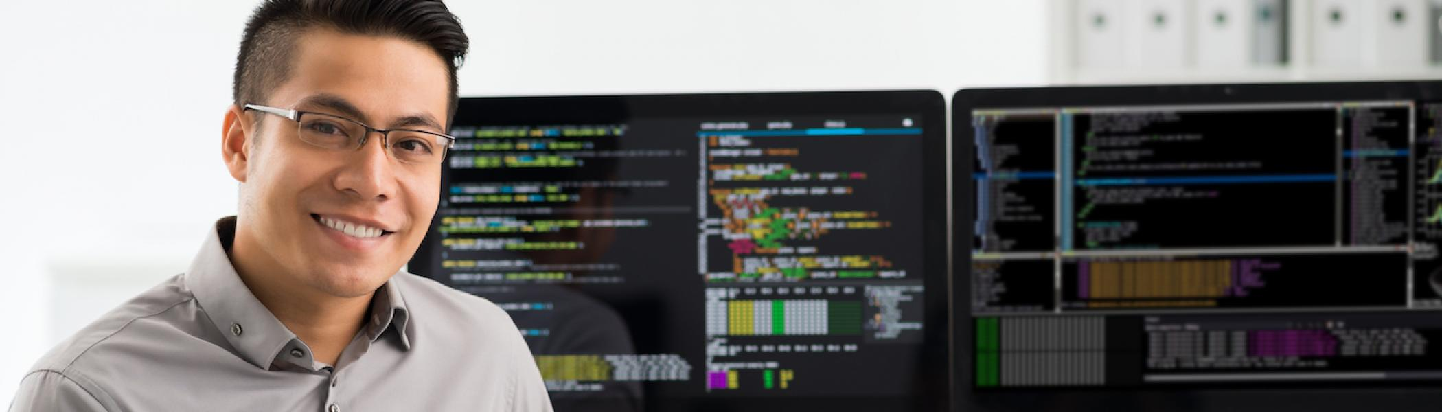 A man siting in front of a computer with code on it, smiling to the camera