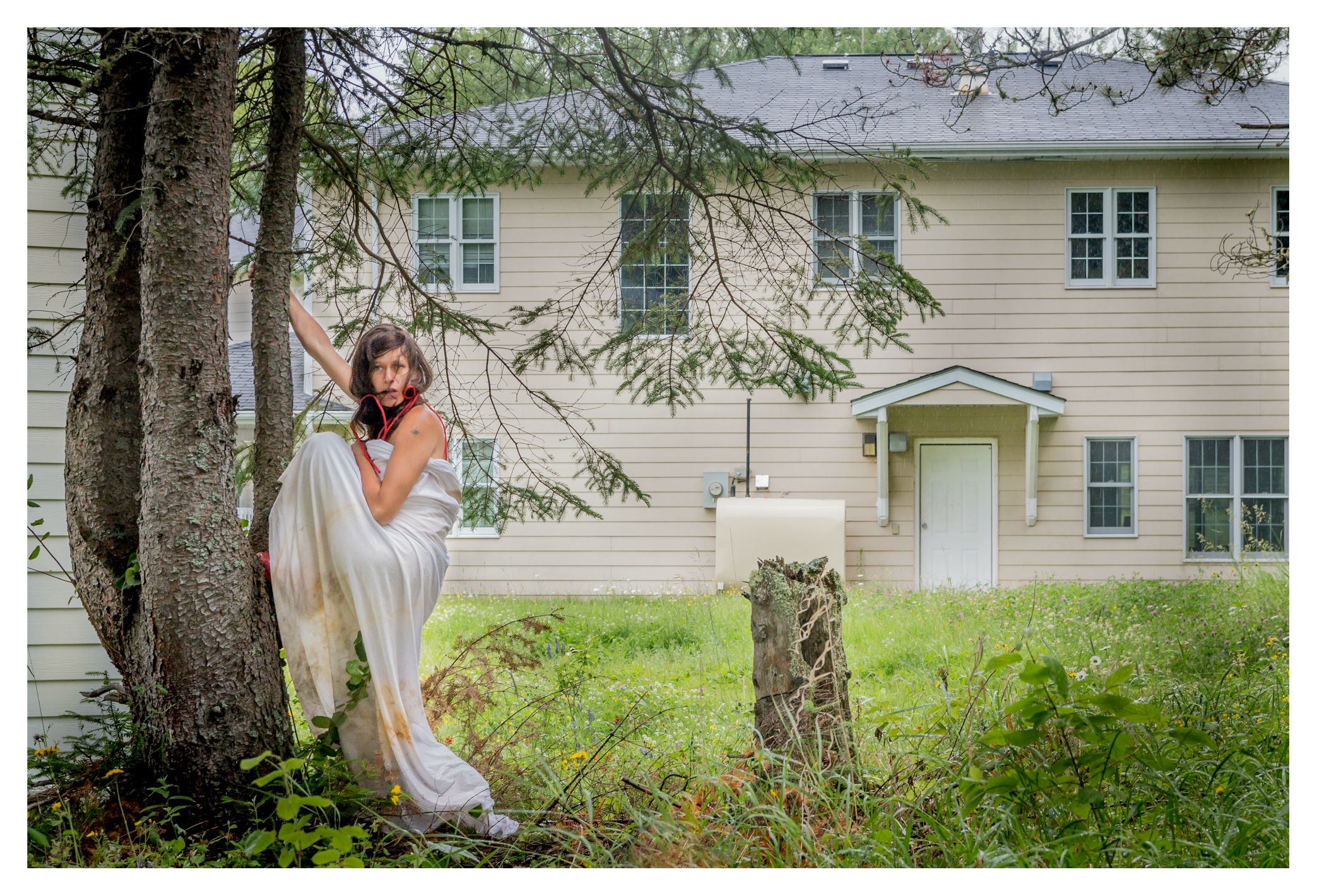 The photo is on the grounds of the former Pelican Lake Indian Residential School. Artist Lara Kramer is standing at the base of a tall conifer tree. Kramer is looking into the distance to the right with a frightened expression in her eyes. She is wrapped in a long white sheet at her chest that drapes below her feet and which has dirt and red stains at the hem. She is grabbing the tree with her right hand, extending her arm above her head. Her left arm is bent with her elbow resting in the crease of her left thigh as she prepares to mount the tree with her left leg bent and left foot in the crease of the tree which she can reach while her right food is on the ground. She is standing amidst thigh high tall plants. There is a red band or string wrapped around her left foot that follows up to her left upper arm, lower jaw, left shoulder, and upper back. There is a white two storey building with horizontal siding immediately left and behind the tree, and another two storey yellow building with horizontal siding in the near distance. There is a tree stump to the right of the artist.