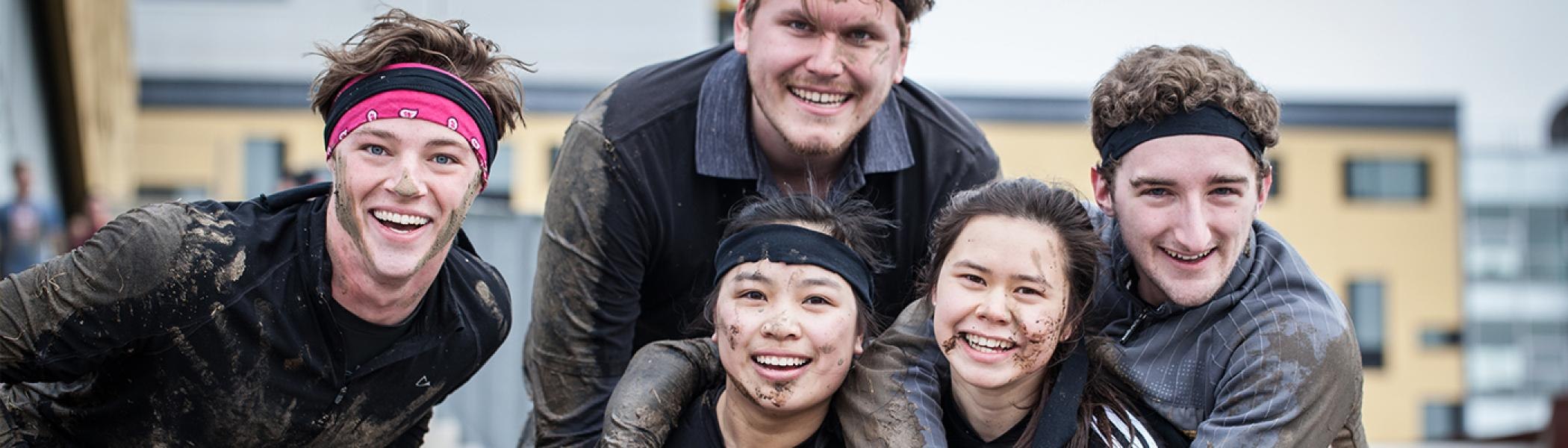 5 students partially cover in mud smiling at the camera