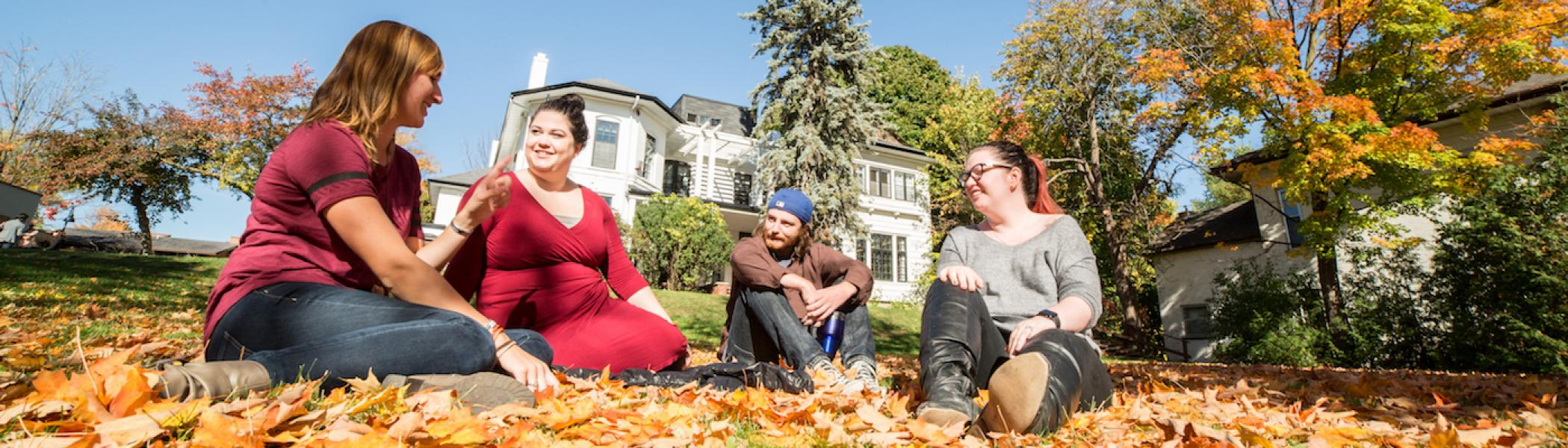A group of students sitting on the lawn in front of Scott House