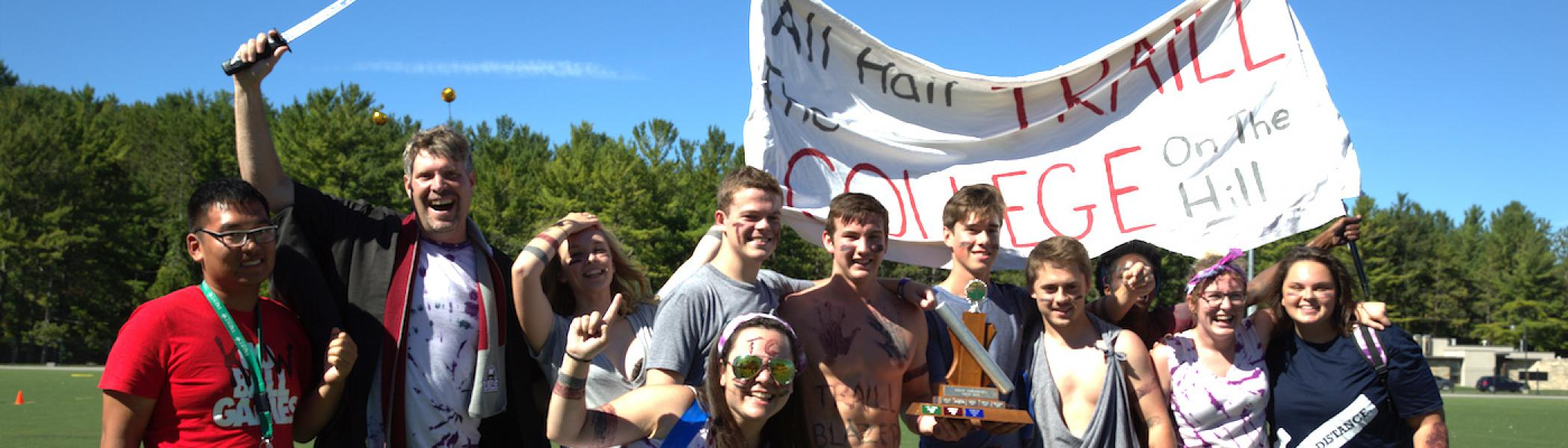 "A group of people smiling and holding up a sign that reads: ""All Hail Traill The College on the Hill"""