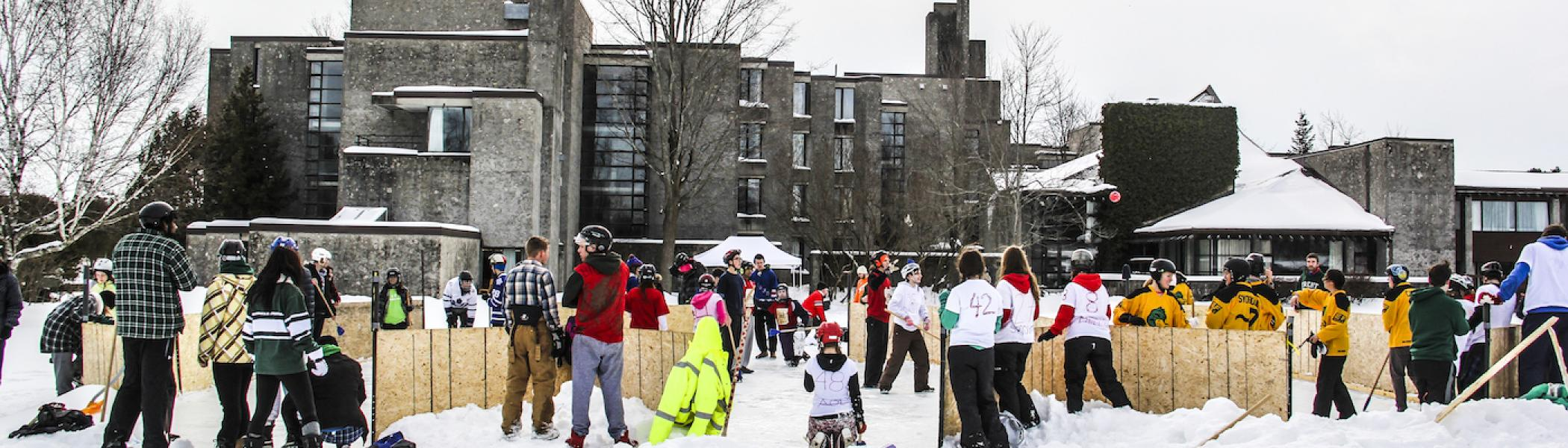 People playing hockey behind Champlain College in the winter