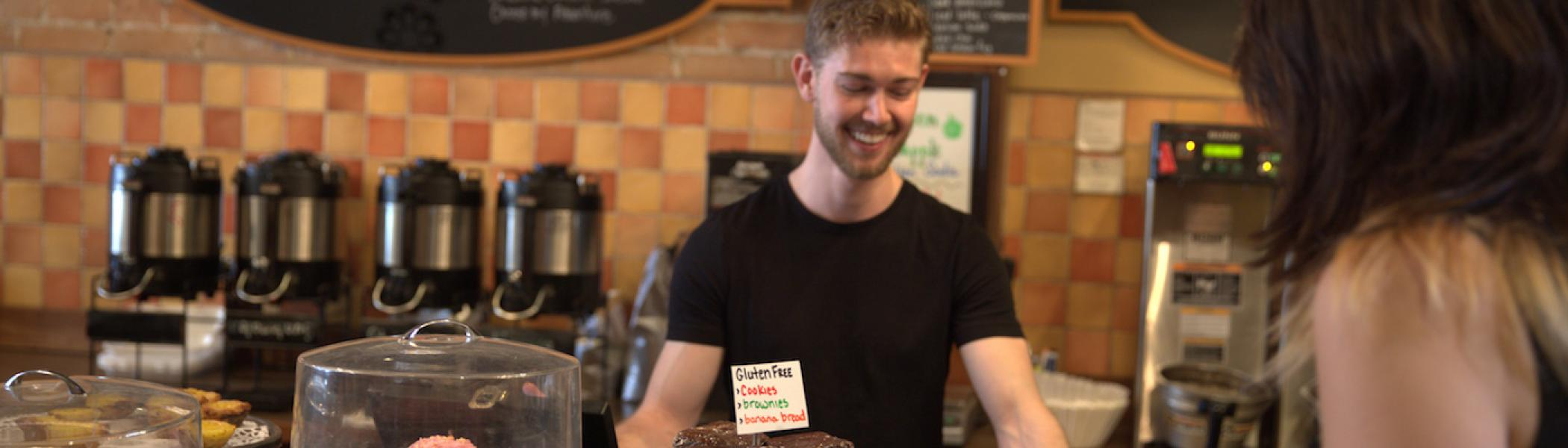 A guy working at a coffee shop smiling at a customer