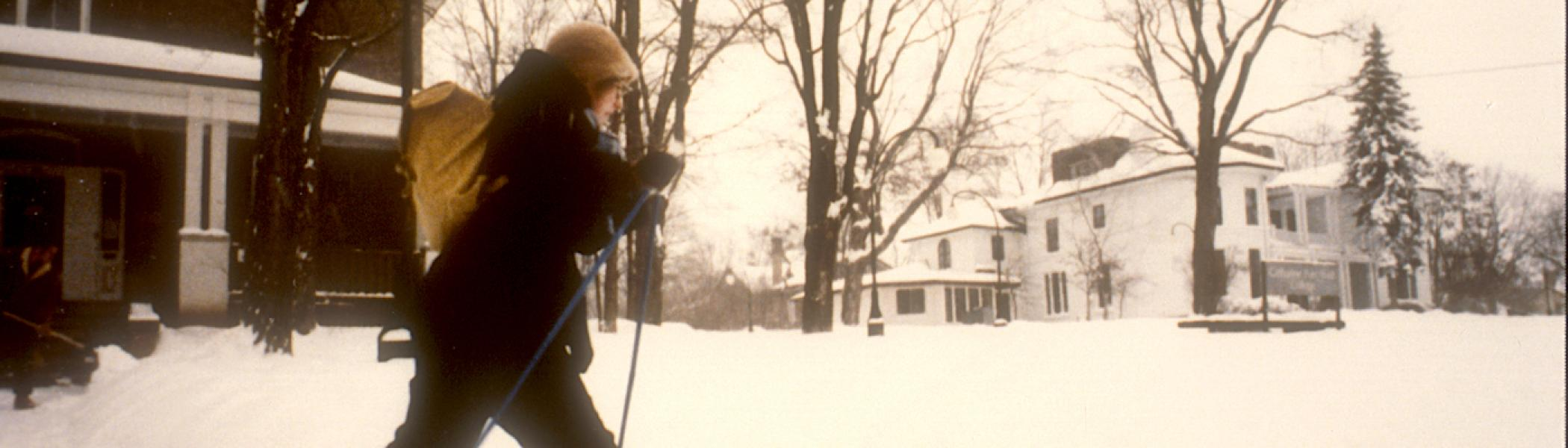 An old photo of a girl skiing through Traill College Campus