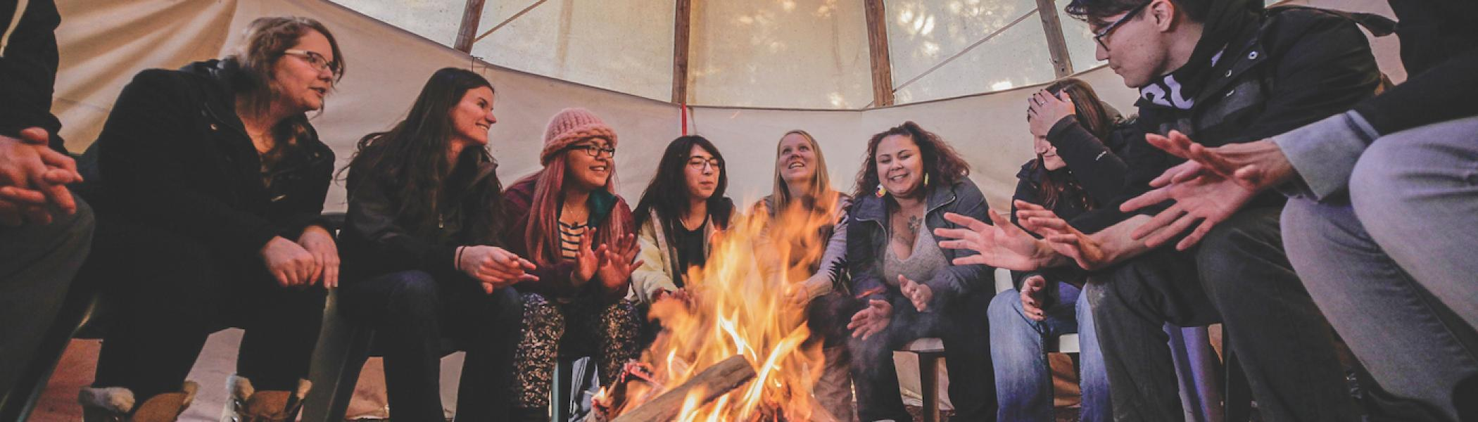 A group of girls sitting around a fire in a tipi at Trent
