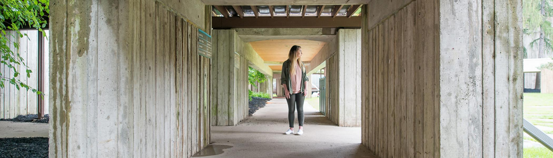Student standing in the overhang of the Lady Eaton College Quad.