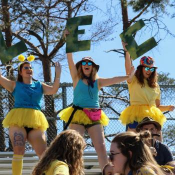Photo from Orientation Week with three students in funny costumes standing on bleachers.