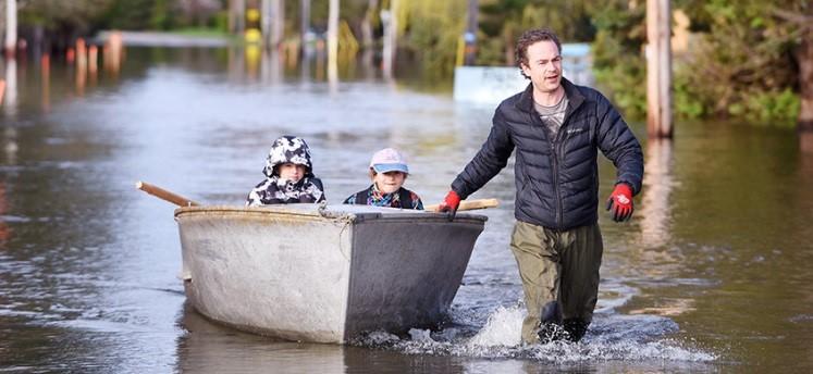 family wading through flood waters