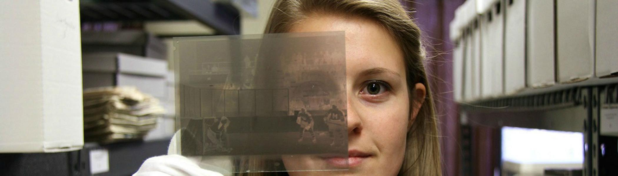 Student holding up a photo negative as part of a community-based research project.