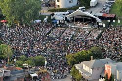 An aerial photo of the Peterborough music festival, with a stage surrounded by thousands of people.