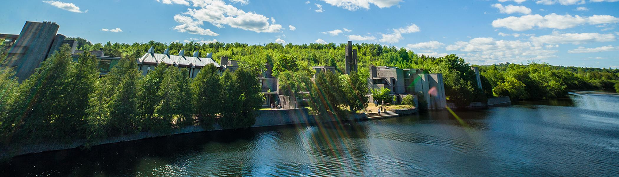 Exterior view of Champlain college in the summer sun from the east bank of the Otonabee river
