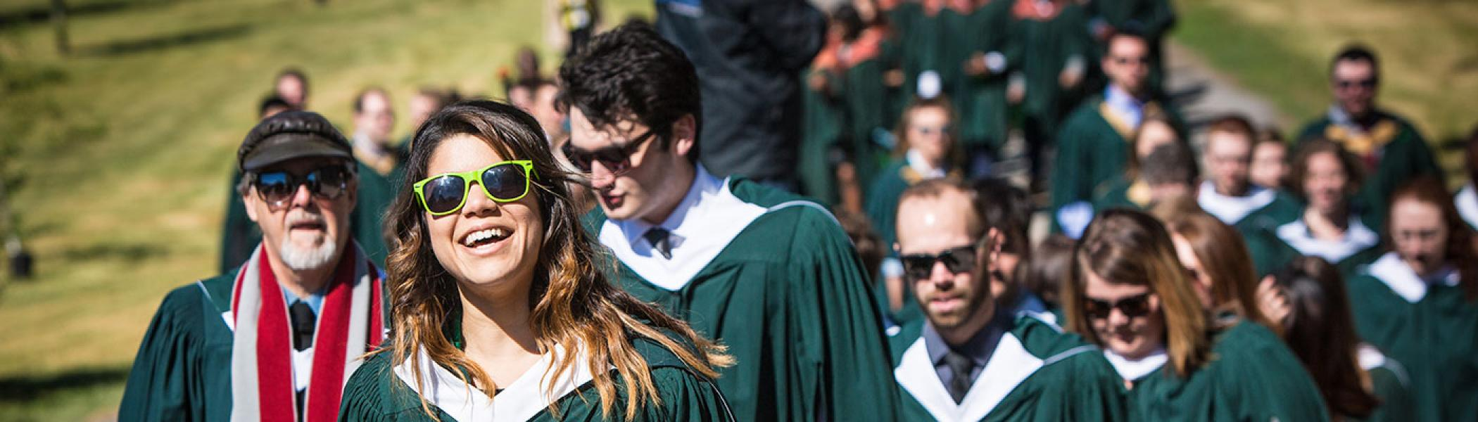 A female student walking across the Bata law in a long line of students, smiling, in her convocation gown on a sunny afternoon