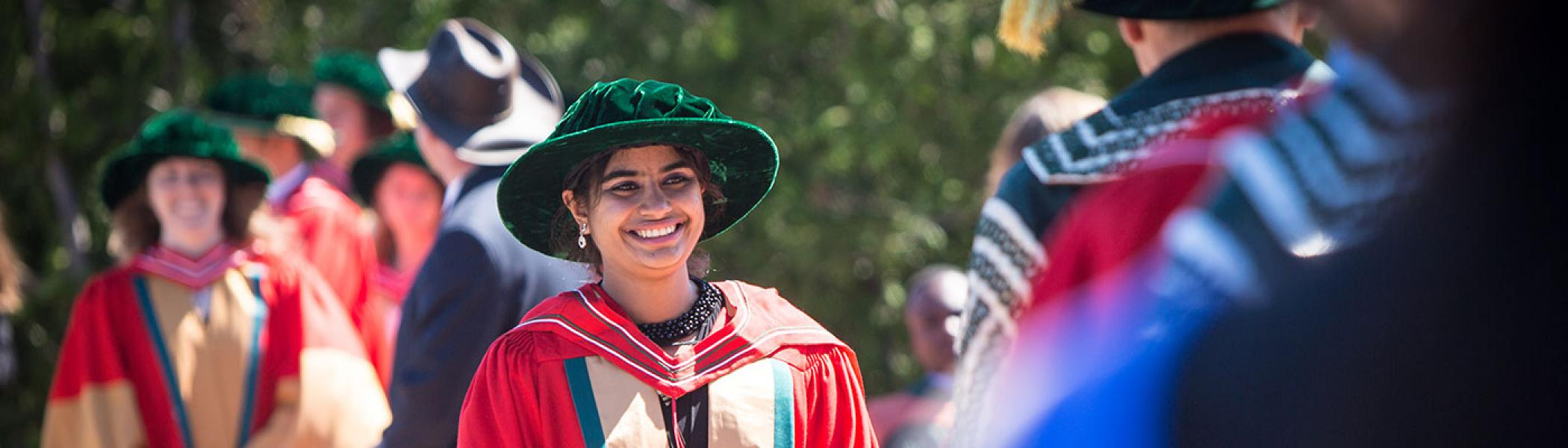 A female student walking across the Bata podium, smiling, in her convocation gown on a sunny afternoon