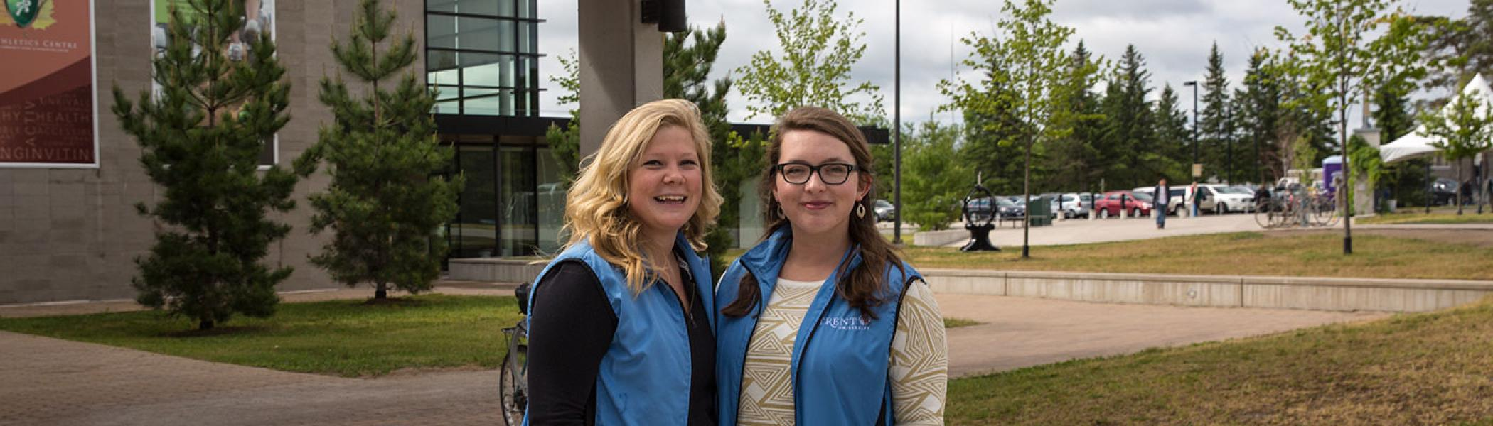Two women dressed in the blue Trent University convocation vests, smiling at te camera, outside in front of the Atheltic's Centre