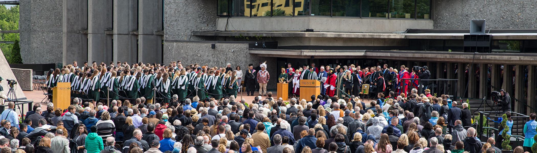 Exterior view of a convocation ceremony on the podium of the Bata library in summer sun