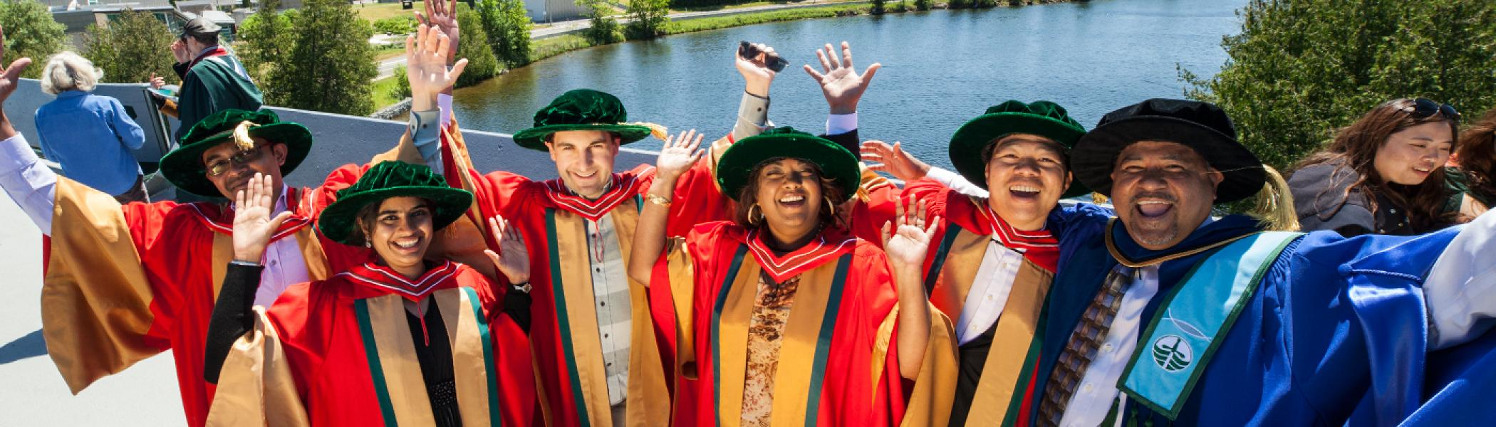 A row of recent doctoral graduates standing on the Faryon bridge with Dr. Suresh Narine with the river in the background on a sunny afternoon during convocation