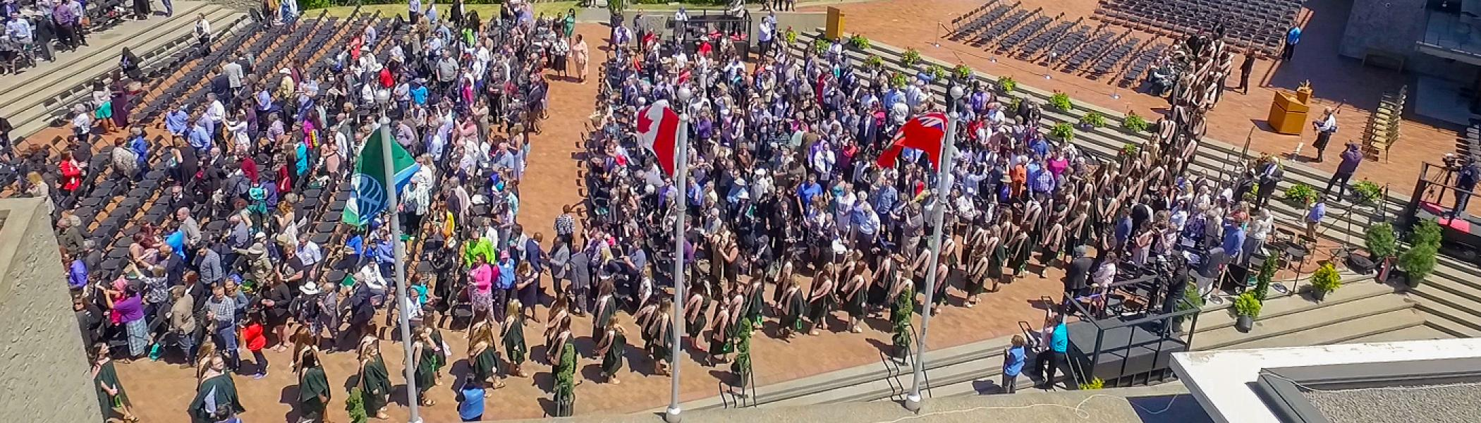 Aerial view of a convocation ceremeony outside on the Bata podium in the summer sun