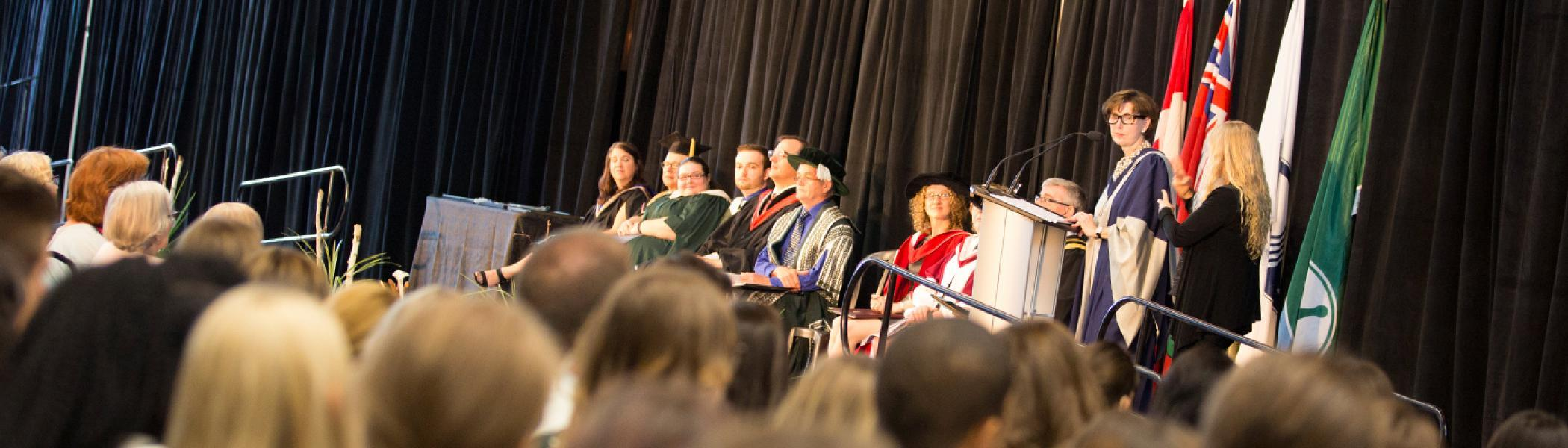 Kathleen Taylor standing at the convocation podium in Durham speaking in the microphone to the graduates sitting in front of her