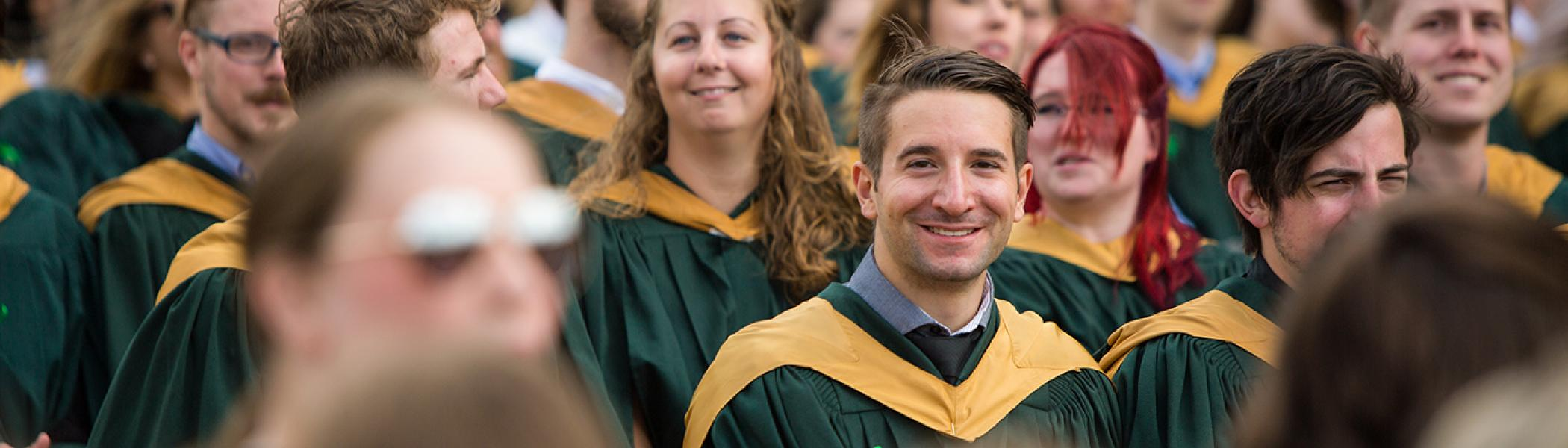Male student in crowd of graduates smiling at the camera and wearing a green gown with gold trim on the hood.