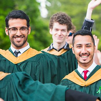 3 students in their convocation gowns smiling at the camera in front of a row of trees