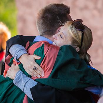 A male student in convocation gown hugging a professor on the Bata podium in the summer sun