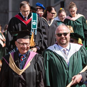 Faculty and staff walking towards the camera, in two rows, after stepping off of the Bata Podium during convocation, on a sunny afternoon