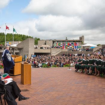 Exterior view of a convocation ceremony on the Bata library podium in the summer sun