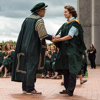 Dr. Don Tapscott shaking hands with a male student on the Bata Podium during a convocation ceremony in the afternoon sun