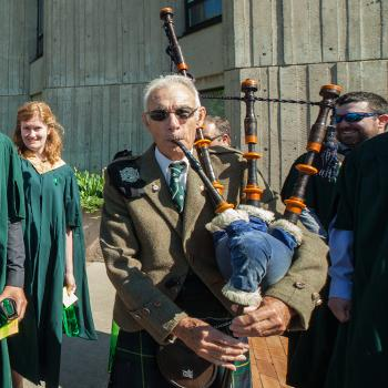 Bag piper playing as he walks in a line of convocating students across the Bata podium on a sunny afternoon