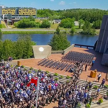 Aerial view of a convocation ceremeony outside on the Bata podium in the summer sun, theotonabee river in the background