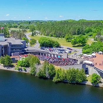 Aerial view of the Bata library and the Otonabee river during a convocation ceremony in the summer sun