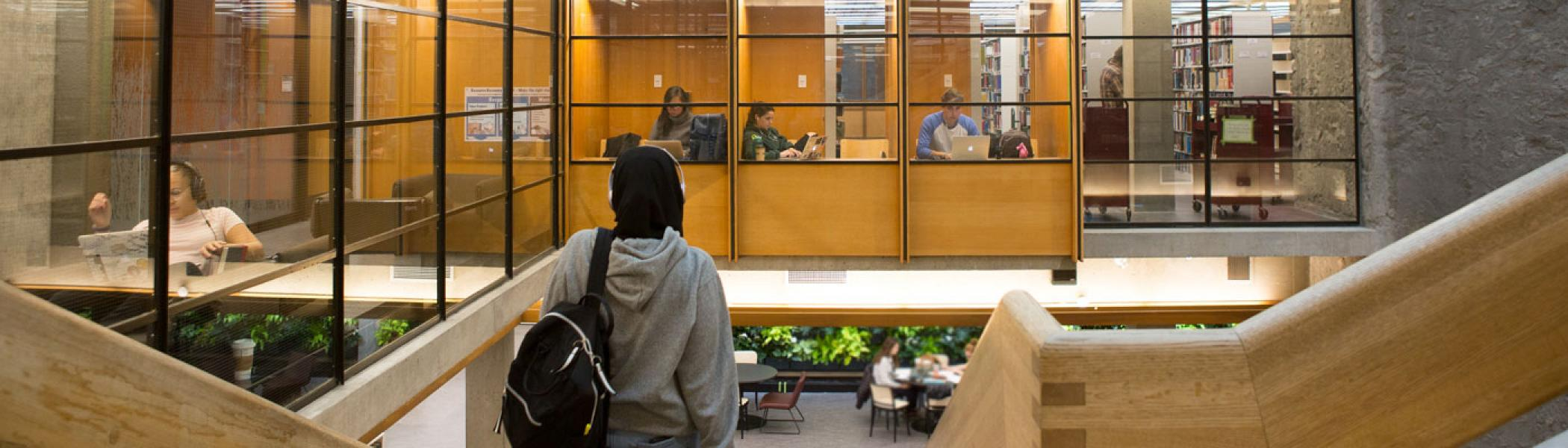 Student walking down the stairs in Bata Library