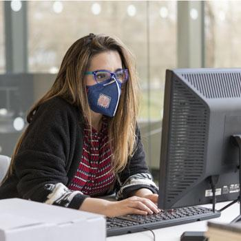 Person wearing a mask working at a desktop