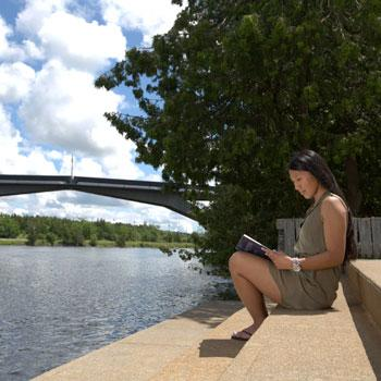 Student studying by the Otonabee River