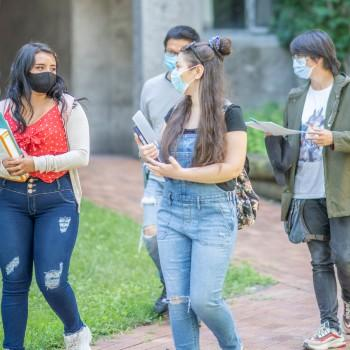 Four international students  walking with books across campus
