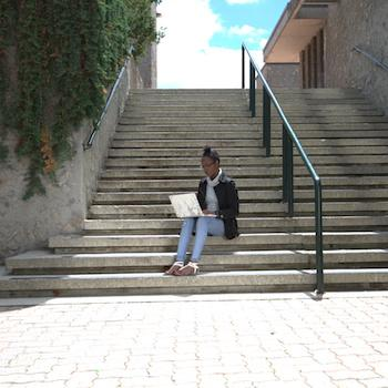 student studying on steps outdoors