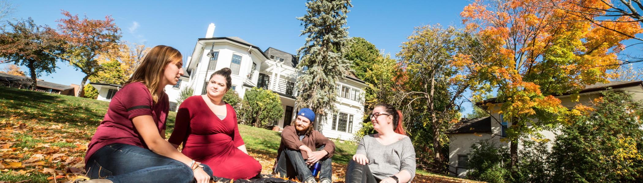Students sitting and talking in front of Scott House, Traill College.