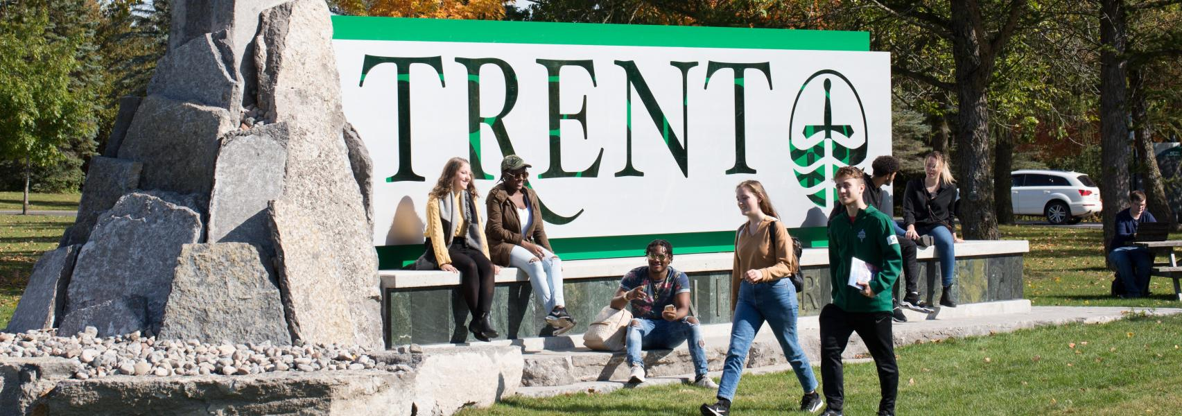 Trent University Peterborough Campus sign with students lounging around.