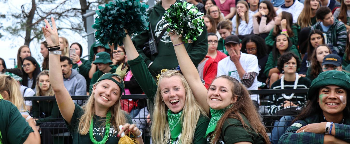 Trent students cheering at Justin Chiu Stadium during a lacrosse varsity game dressed Trent University spirit-wear.