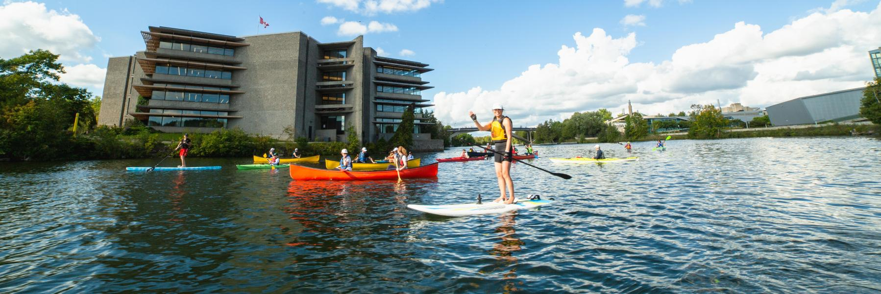 Students in canoes and on paddle boards on the Otonabee River boating past Bata Library.