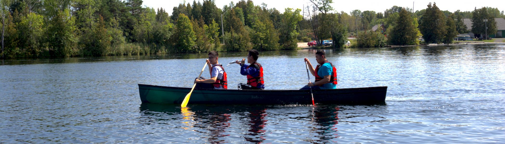 3 students in a canoe on the Otonabee river
