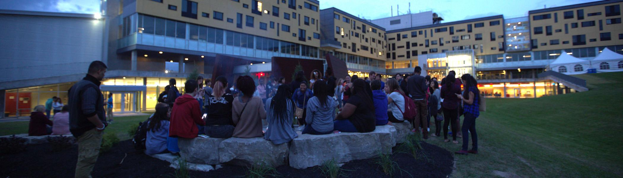 A large group of international students sitting around a campfire in front of Gzowski College at night