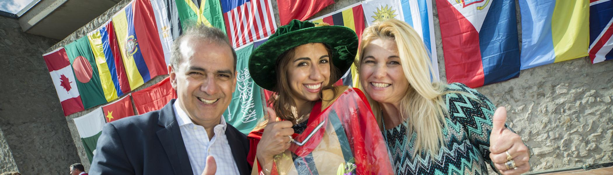 A graduate with her parents smiling and giving the thumbs up in front of a wall of flags