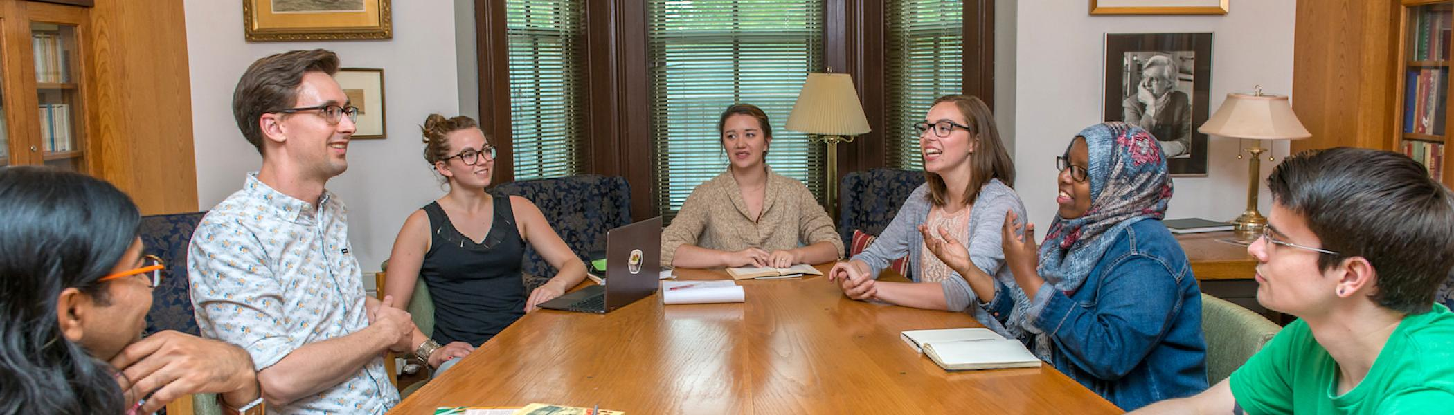 A group of students with a faculty member sitting at a table and talking to each other and smiling